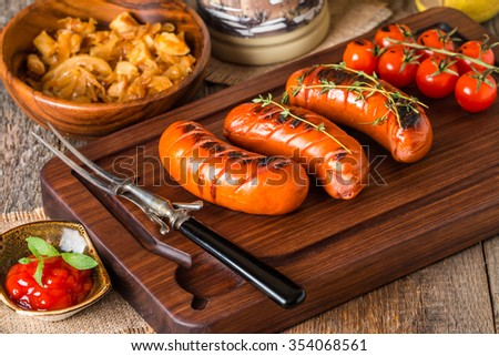Grilled sausages with cabbage, tomato and glass of beer on wooden cutting board - stock photo