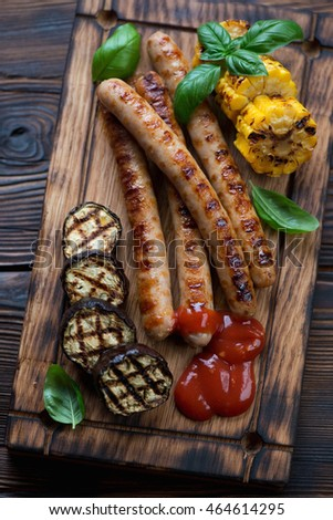 Grilled sausages with eggplants, corn and ketchup, closeup