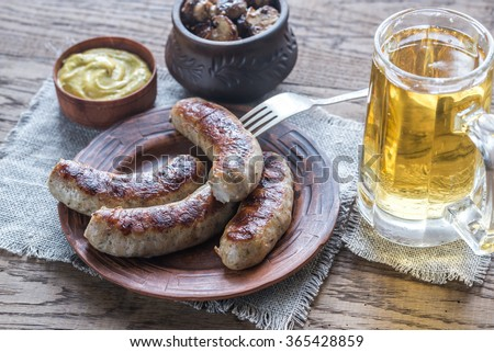 Grilled sausages with fried bacon rashers and mushrooms - stock photo