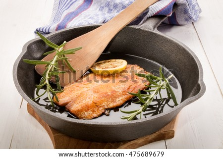 grilled Scottish kipper with oil and rosemary in a cast iron pan