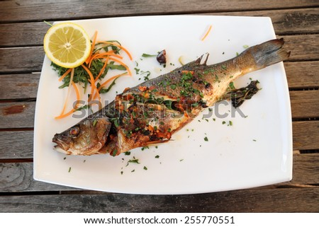 Grilled sea bass Fish plate on wooden table  ,serving in maltese  restaurant - stock photo