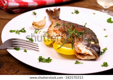 Grilled sea bream fish, lemon on white plate, soft focus - stock photo
