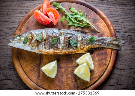 Grilled seabass on the wooden board - stock photo