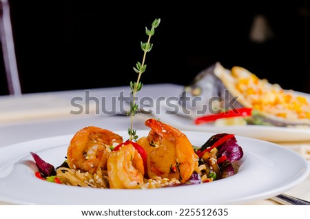 Grilled shelled pink prawns and scallop with rice and vegetables served on a restaurant table with dark background and copyspace