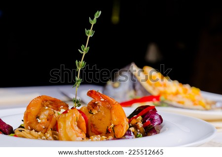 Grilled shelled pink prawns and scallop with rice and vegetables served on a restaurant table with dark background and copyspace - stock photo