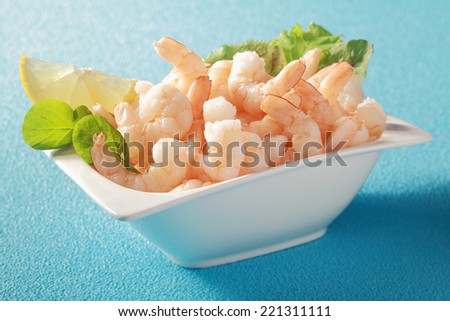 Grilled shelled pink prawns served in a white dish with fresh leafy green herbs as a gourmet appetizer to a dinner, on a blue table - stock photo