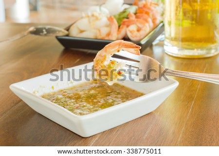 grilled shrimp on a fork with sea food sauce on wood table, Thai food - stock photo