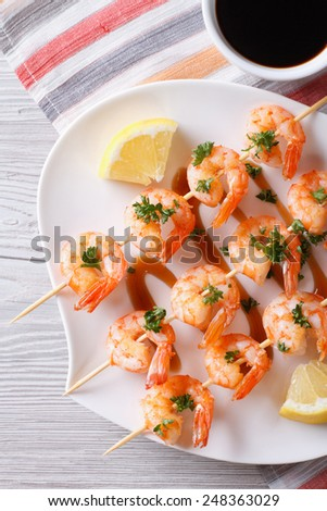 Grilled shrimp on skewers with lemon on a plate close-up. vertical top view  - stock photo
