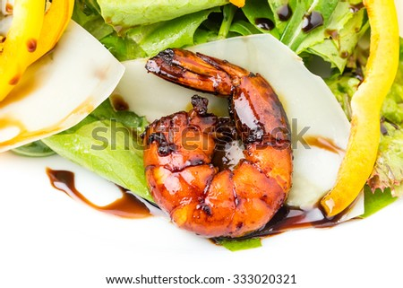 Grilled shrimp salad with sliced parmesan and fresh herbs. Covered with dark soya sauce. Macro. Photo can be used as a whole background. - stock photo