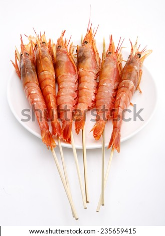 Grilled shrimp string up on the white plate isolation on white - stock photo