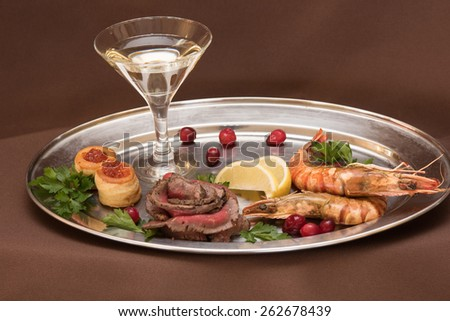 Grilled shrimps and beef meat on a plate - stock photo