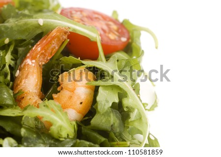 grilled shrimps, cherry tomatoes and aragula leaves on a plate