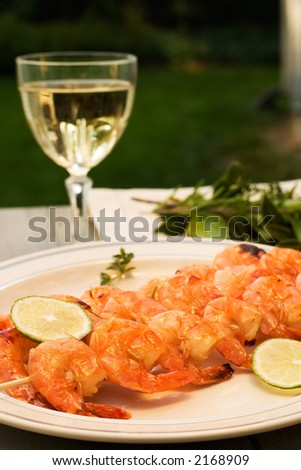 Grilled shrimps on bamboo sticks served with limes, thyme twig and glass of white wine are served outside - stock photo