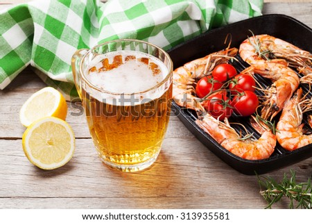 Grilled shrimps on frying pan and beer on wooden table - stock photo