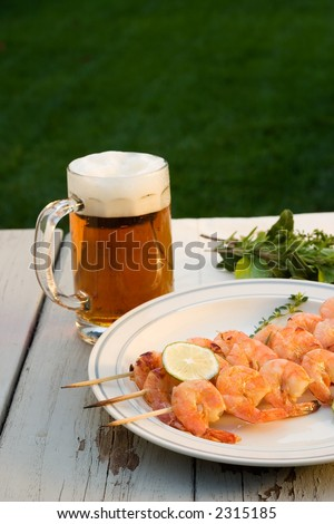 Grilled shrimps on wood sticks served on outside table with lime and mug of pale ale
