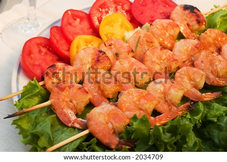 Grilled shrimps on wood sticks served with tomatos and green salad are ready to eat - stock photo