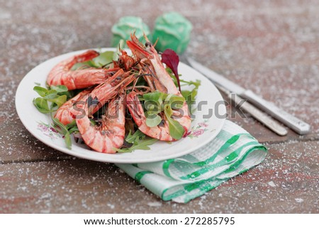 Grilled shrimps served outdoor in winter, snow on table, toned image - stock photo