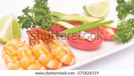 grilled shrimps with vegetables on white plate