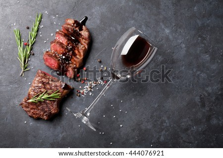 Grilled sliced beef steak with balsamico and rosemary and red wine on stone table. Top view with copy space - stock photo