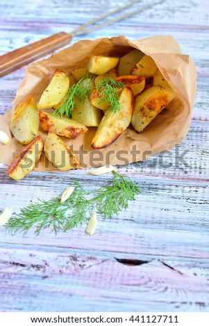 Grilled slices of potato in a paper on the table - stock photo