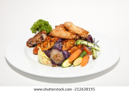 Grilled steak and chicken with vegetables on a white background