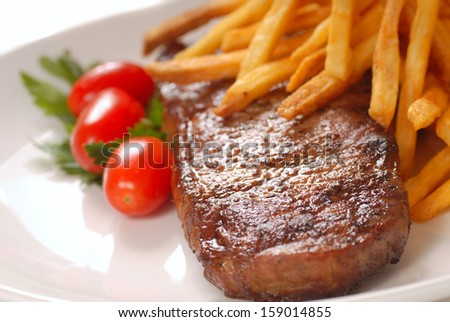 Grilled steak and french fries with tomatoes