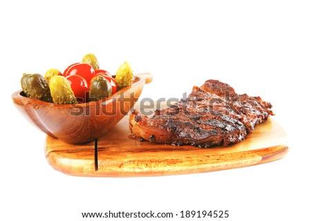 grilled steak entrecote and vegetables on wooden plate isolated over white background - stock photo