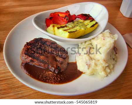 Grilled steak, garlic mashed potatoes and vegetables on white plate at a restaurant