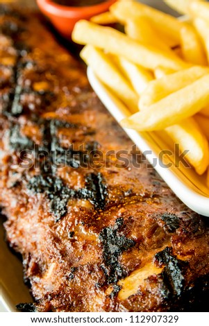 Grilled steak - Grilled meat ribs on the plate with hot sauce