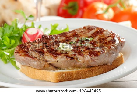 Grilled steak on toast bread, served with onion and vegetable and a glass of good wine