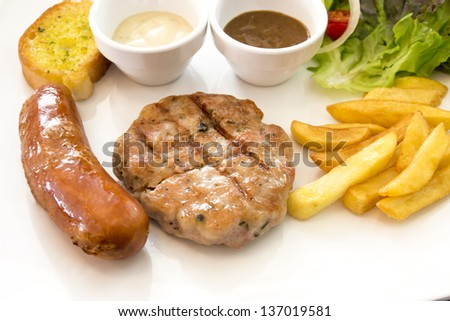 Grilled steak  Sausage Garlic Bread French fries and vegetables