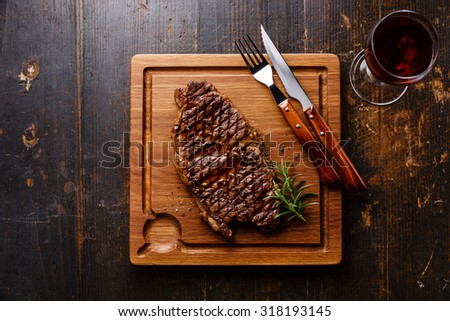 Grilled Steak Striploin and red wine on cutting board on dark wooden background - stock photo