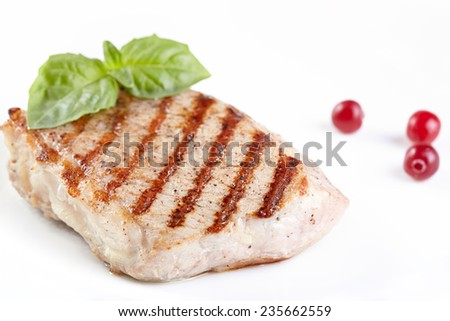 Grilled steak with a cranberry on white plate - stock photo