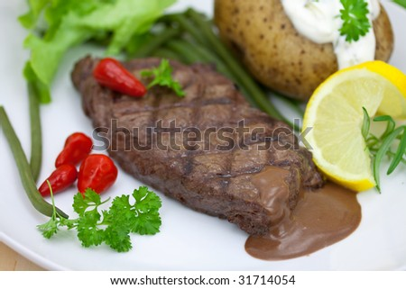 grilled steak with baked potato and cream