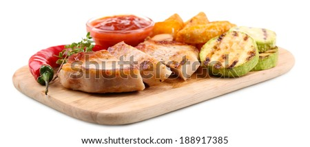 Grilled steak with fried potato pieces and grilled vegetables  on wooden board, isolated on white