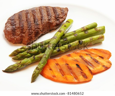 Grilled steak with green asparagus and carrot - stock photo