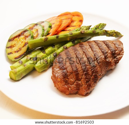 Grilled steak with green asparagus, carrot and zucchini - stock photo