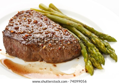 Grilled steak with Green asparagus on white background - stock photo