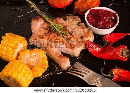 Grilled Steak with Grilled Vegetables and cranberry sauce. Steak on black background. Selective Focus.  - stock photo