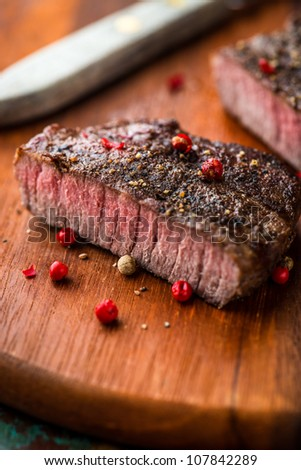 Grilled steak with peppercorns on wooden chopping board - stock photo