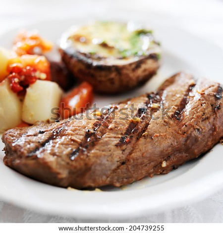 grilled steak with potatoes and stuffed mushroom - stock photo