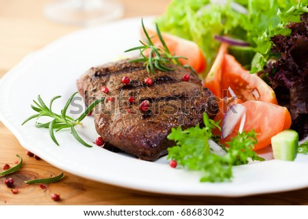 Grilled steak with salad and herbs - stock photo