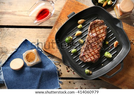 Grilled steak with spice, garlic and Brussels sprouts on grill pan - stock photo