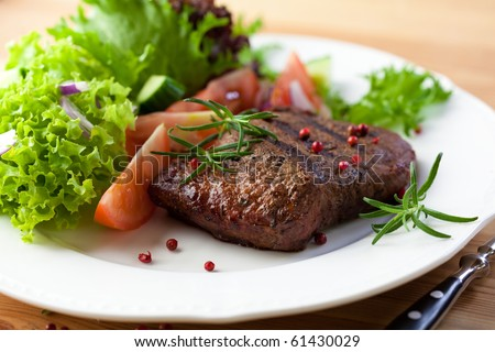 Grilled steak with vegetable salad and herbs - stock photo