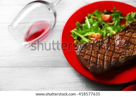 Grilled steak with vegetable salad and wine, closeup - stock photo