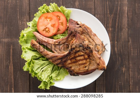 Grilled steak with vegetables on a wooden background - stock photo