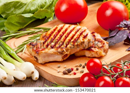 Grilled steak with vegetables on a wooden board - stock photo
