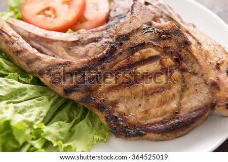 Grilled steak with vegetables on white dish.