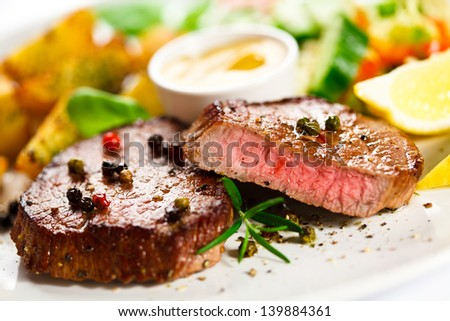 Grilled steaks, baked potatoes and vegetable salad - stock photo