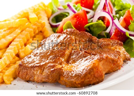 Grilled steaks, chips and vegetable salad - stock photo